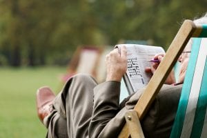 senior doing crossword in park to keep mind young