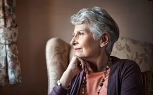 senior women sitting at window worried
