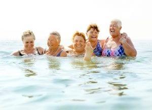 happy senior women splashing in cool lake