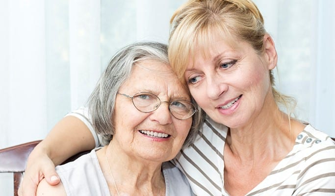 woman with half smile has arm around senior mom