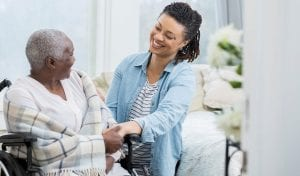 In home care worker helping elderly women in chair