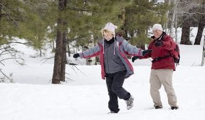 Active retired couple playing in the snow