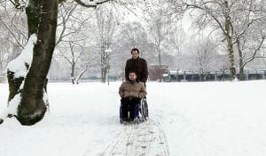 man helping someone in wheelchair through snow
