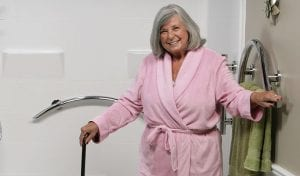 Senior women in pink robe holding chrome designer grab bar in bathroom