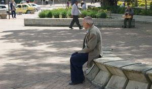 elderly man sitting on a bench outside