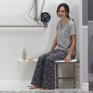 Female in pjs sitting on white ADA shower seat in shower