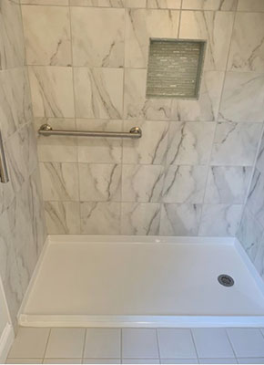 Freedom 60 by 36 shower pan installed with marble tiles walls and grab bar