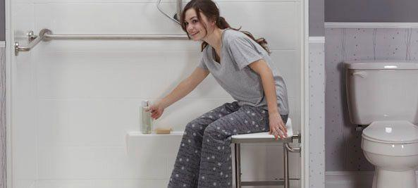 young women sitting on wall mounted folding bench in shower