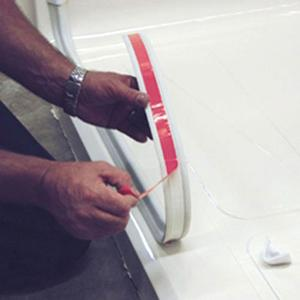 collapsible water dam with adhesive strip